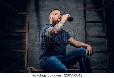 Brutal Bearded Tattooed Male Drinking Beer From A Bottle In Grey Vignette Background With Two Wooden