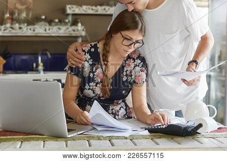 Young Family Couple Consider Mortgage Loan Offer, Calculate Interest On Debt, Pose Against Kitchen I