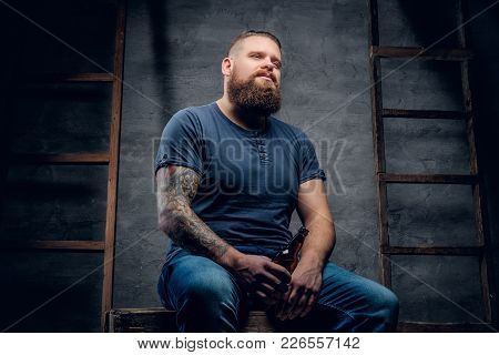 Studio Portrait Of Bearded Tattooed Hipster Male Holds The Beer Bottle On Grey Background With Two V