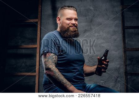 Bearded Tattooed Hipster Male Enjoys Of A Beer.