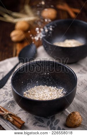 Levitating Flakes Of Oatmeal. Still-life On A Wooden Background. Oatmeal Flakes, Nuts And Cinnamon S