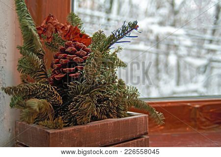 Concept Cozy Winter Evening. Still Life: Coniferous Branches And Pine Cone Against Background Window