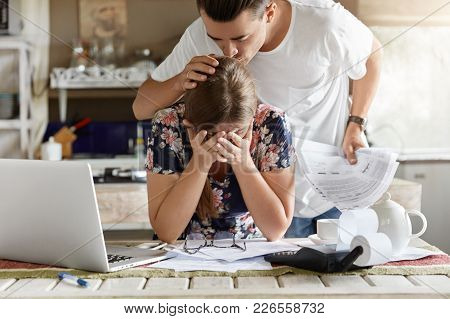 Sad Woman Covers Face With Hands, Feels Desperate And Embarrased, Recives Bank Invoice Or Bill, Sit