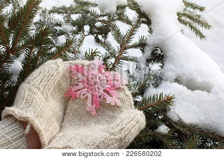 Snowflake Knitted From Pink Thread In Warm Mittens On Background Of Winter Landscape / Gift With A W