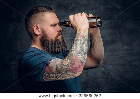 The Bearded Hipster Male With Tattoo On Arm, Looking Through Beer Bottle.