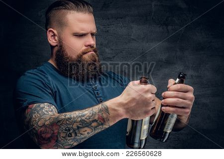 Alcohol Addiction. Bearded Male Looking At Two Empty Beer Bottles.