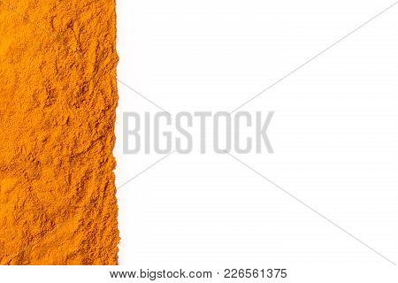Curcuma Ground Powder Isolated On White Background. A Band Or Streak Of Curcuma Is Located On The Le