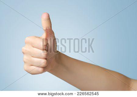 Female Thumb With Adhesive Bandage On Blue Background