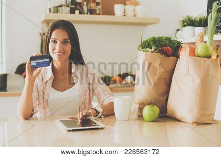 Young woman in the kitchen, using her ipad. Young woman