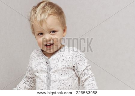 Playful Disheveled Cute Baby Looking At Camera Against Grey Background. Copy Space.