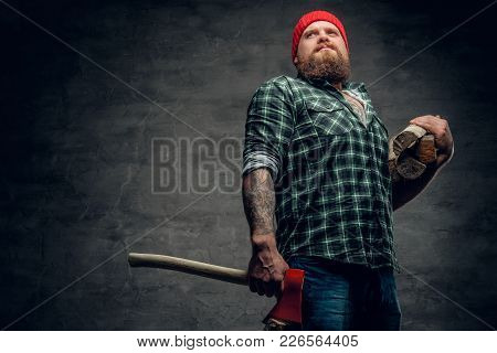 Portrait Of Bearded Lumberjack Dressed In A Green Shirt Holds Red Axe.