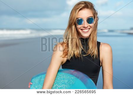 View Of Pleasant Looking Blonde Woman In Sunglasses, Relaxes On Seashore, Involved In Active Water S