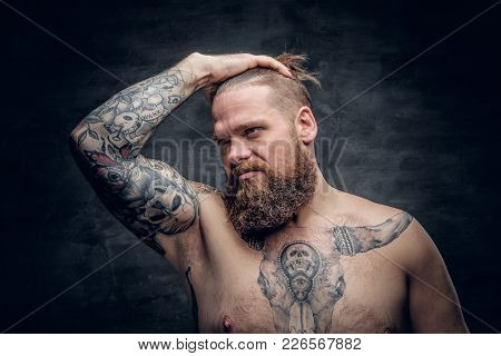 Portrait Of A Shirtless Bearded Male With Tattooed Arm And Bull Tattoo On A Chest.