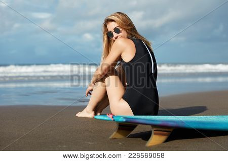 Slender Beautiful Young Woman In Shades Sits On Sandy Beach, Ready For Surg Ride With Surfboard, Dre