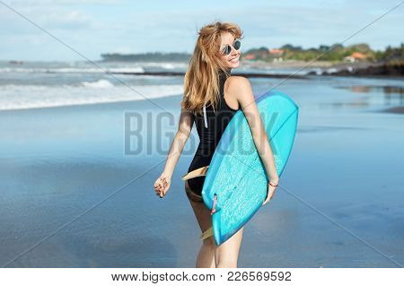 Attrative Slender Young Female Model With Blonde Hair, Dressed In Swimsuit And Wears Sunglasses, Hol