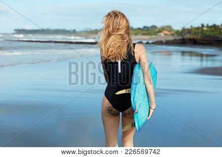 Back View Of Adorable Sexy Woman In Bikini, Has Sporty Booty, Holds Surfboard, Walks At Beach, Relax