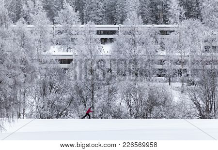 Umea, Sweden On January 13. View Of Frosty Trees, Block Of Houses And A Lonely Cross-country Skier O