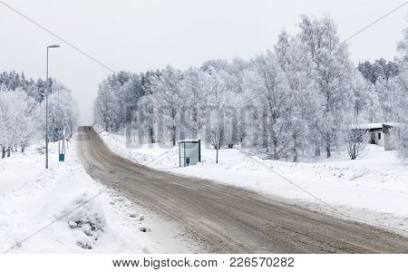 View Of A Snowy Street, A Bus Stop And Frosty Trees. Hill And Trees In The Background. Winter.