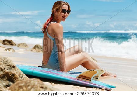 Delightful Happy Female Surfer Sits At Wet Sandy Beach With Surf Board, Going To Have Surfing Exerci