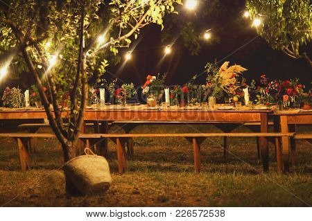 Prepared Table For A Rustic Outdoor Dinner At Night With Wineglasses, Flowers And Lamps In The Garde