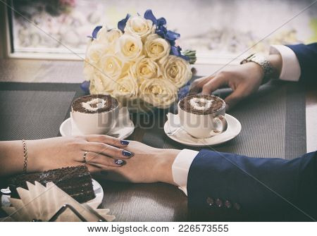 Filming By A Close Up Of The Hands Holding Warm Coffee. Newlyweds Have Coffee.