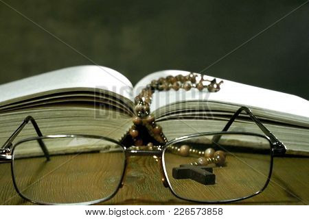 Open Bible With Glasses On The Old Table.