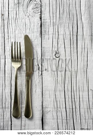 high angle view of a golden fork and a golden knife on a white rustic wooden table with a blank space on the right