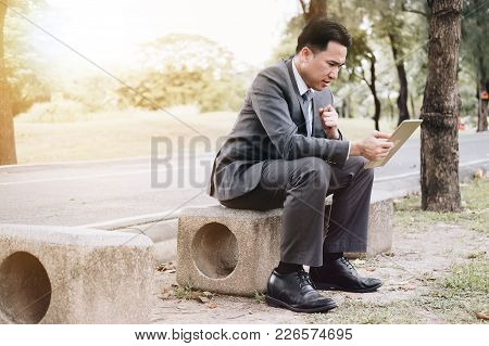 Businessman Stressed Out With Sale Report With Tablet Computer Report In The Garden