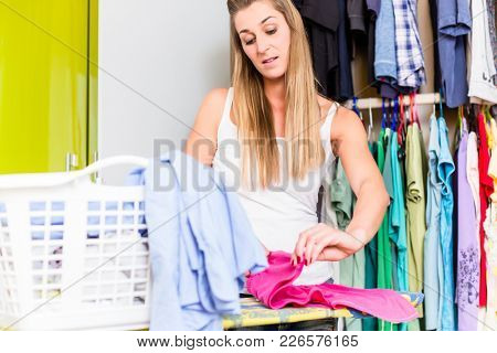Woman in front of wardrobe in bedroom folding clean laundry