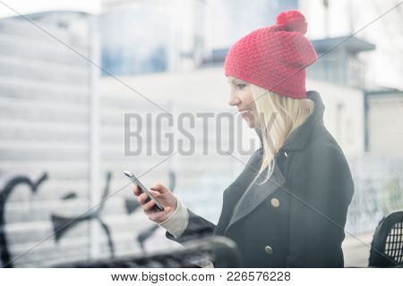 Woman using her phone while waiting for a suburban train
