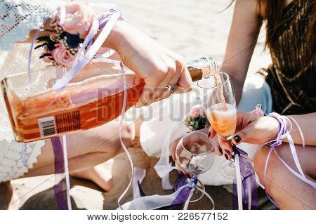 Girl Pours Champagne Into Glass. Happy Slim Stylish Sexy Young Girls Sand Beach. Glass, Hand Decorat