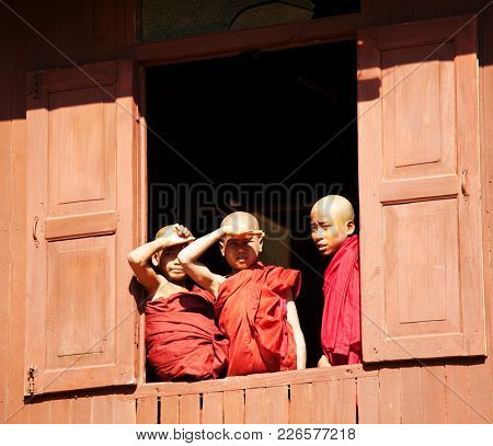 INLE LAKE, MYANMAR - FEBRUARY 02: Young monks are watching from monastery oval window on February 02, 2011 in Shwe Yaunghwe monastery in Nyaungshwe, Shan state of Myanmar