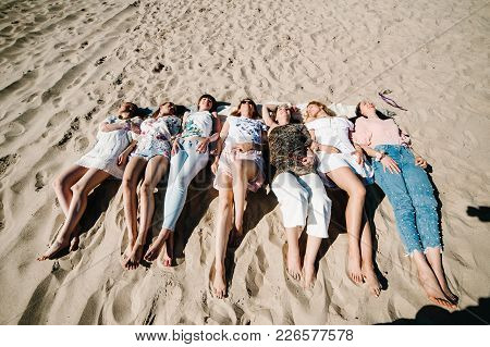 Beautiful Happy Slim Stylish Sexy Girls Lying Down On Sand Beach Show Long Legs. Party In Style Boho