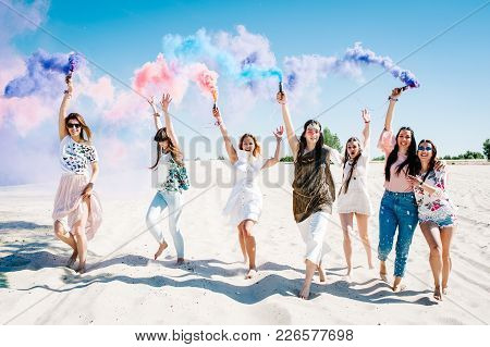 Beautiful Happy Stylish Sexy Young Girls Stand Beach And Hold Light Up Colored Smoke Bombs. Burn Up.
