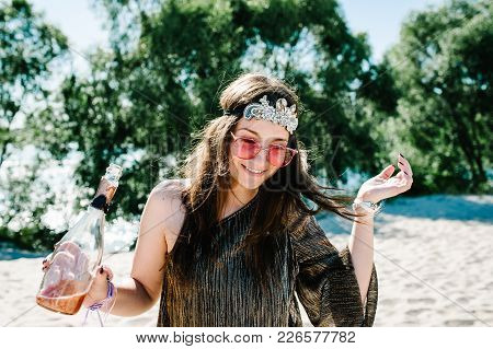 Beautiful Happy Sexy Stylish Young Girl With Glass Wine, Champagne Stands On Beach In Nature. Style
