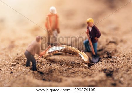 Gold Digging Or Archaeology Concept. Workers Digging Golden Ring Out Of Sand