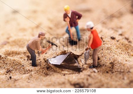Diamond Mining And Treasure Search Concept. Figurines Digging Gemstone Out Of Sand
