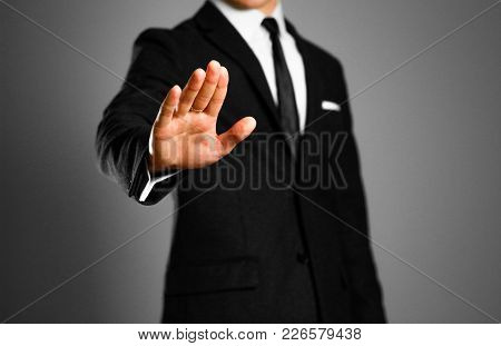 Businessman In A Black Suit, White Shirt And Tie Shows Palm Rejection. Studio Shooting.