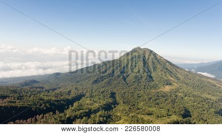 Tops Of The Mountains Covered With Forest In Running Clouds And Fog At Sunrise. Landscape Slopes Of
