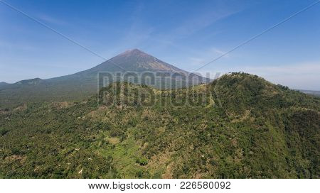 Aerial View Of Volcano Mount Agung With Smoke Billowing Out At Sunrise, Bali, Indonesia. Conical Vol