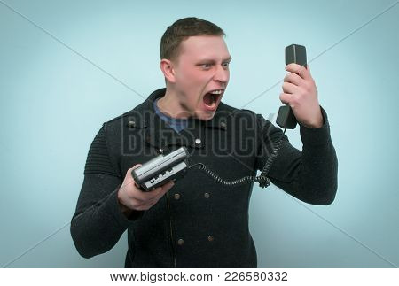 Wicked Vexed And Dissatisfied Hot Line Consultant Man Is Screaming Into A Phone Handset In His Hands