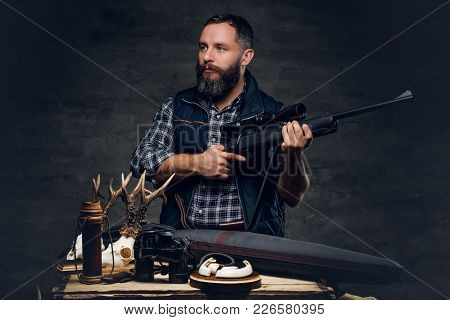 Studio Portrait Of A Bearded Modern Hunter With His Trophy Holds A Rifle.