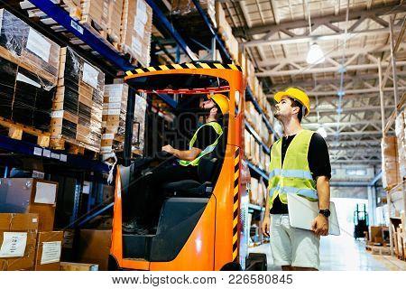 Warehouse Workers Working Together With Forklift Loader Trasnporter