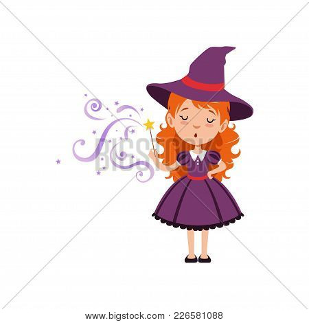 Cute Small Witch Casts A Spell With The Magic Wand. Young Red-haired Kid Girl Wearing Purple Dress A