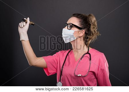 Portrait Of Attractive Lady Doctor Wearing Mask Writing With Marker