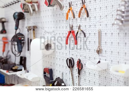 Picture Of Working Tools Hanging On Board In Workshop