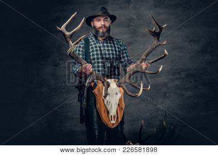 The Bearded Hunter Male Holds A Skull Of A Deer.
