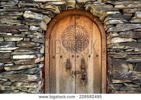Old Wooden Door In The Stone Wall From Medieval Era