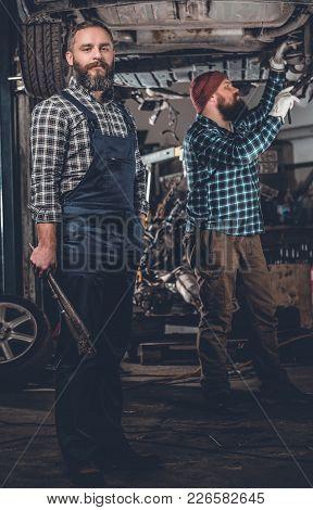 Two Bearded Men Repairing Car In A Garage.