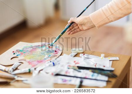 fine art, creativity and artistic tools concept - artist hand with paintbrush, and palette painting at studio